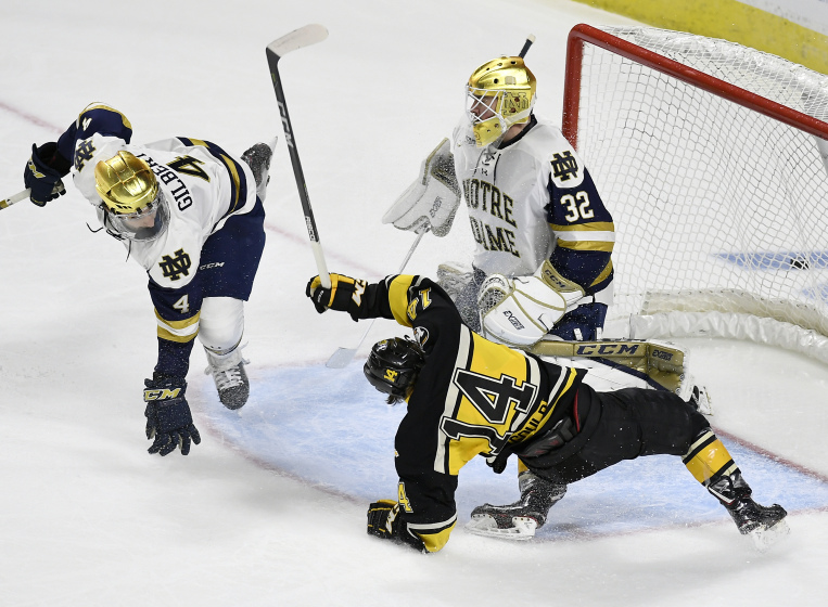 Notre Dame's Dennis Gilbert (4) trips up Michigan Tech's Gavin Gould (14) as he attempts a shot on goal while Notre Dame goaltender Cale Morris (32) defends during the first period of a first round NCAA college hockey tournament game, Friday, March 23, 2018, in Bridgeport, Conn. (AP Photo/Jessica Hill) ORG XMIT: CTJH101